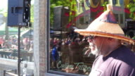 The traditional event is held every Spring in the Canadian city / Afro American drummer performing people walking in the street reflected in the glass