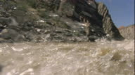 The turbulent Colorado River churns under a whitewater raft. Available in HD.