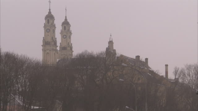 The twin spires of a church tower above a hilltop in Siauliai. Available in HD.