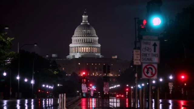 The US Capitol building stands during a rainstorm before sunrise in Washington DC US on Thursday July 6 2017 Shots wide shot in traffic as car lights...
