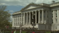 ZO The US Treasury building as reporter discusses the danger of the automotive companies declaring bankruptcy / Washington DC United States