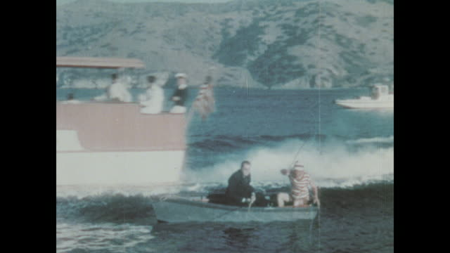 The wake from a larger boat rocks two men in a rowboat
