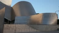 The Walt Disney Concert Hall stands at sunrise in downtown Los Angeles California Shots pan across the modern exterior architecture of the Walt...