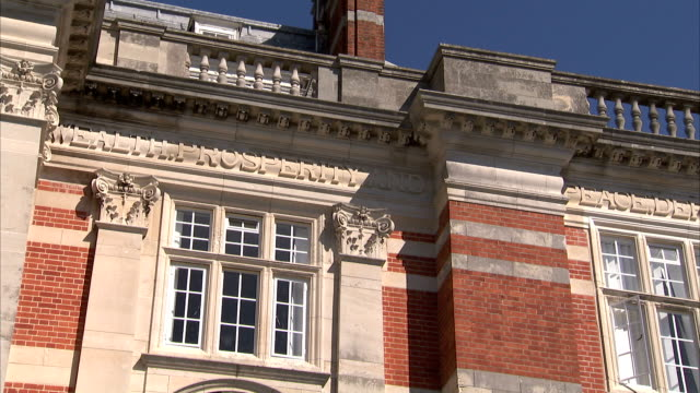 The words 'Wealth' and 'Prosperity' are engraved on the exterior of a building on the campus of Britannia Royal Naval College. Available in HD.
