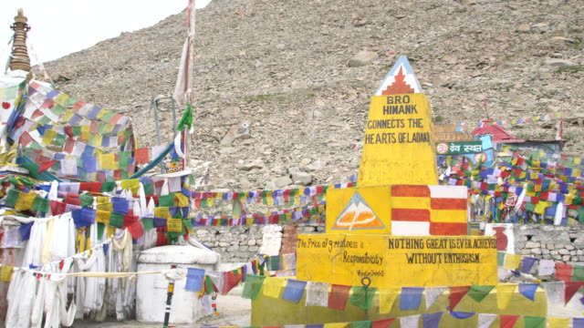 The yellow sign board and prayer flags at the Chang La Pass, Ladakh, India