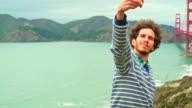 Der junge Mann, touristischen und Hipster, die Dreharbeiten zu des malerischen Blick auf die Golden Gate Bridge, San Francisco, Kalifornien