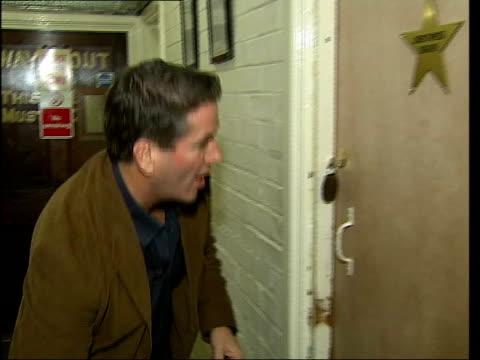 London EXT Garry Trainer along to stage door Trainer knocking on door in theatre actor Christopher Biggins inviting him in Trainer unpacking...
