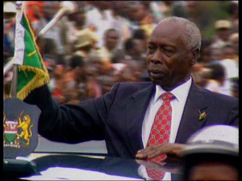 LIB Then President Daniel Arap Moi along in motorcade standing in car and waving to crowds lining street PAN London MS Foreign Office TILT