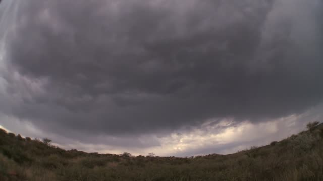 A thick blanket of gray storm clouds drifts above a desert plain. Available in HD.