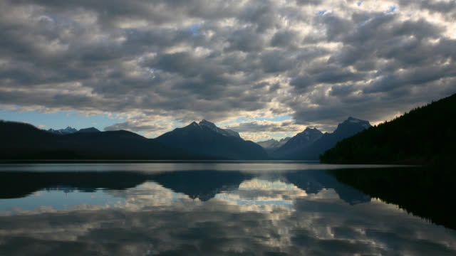 TIME LAPSE WIDE SHOT thick layer of clouds becomes thinner over Lake McDonald and Rocky Mountains in background, Glacier National Park, Montana