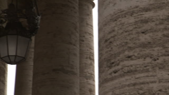 Thick stone columns obscure a view of St. Peter's Basilica.