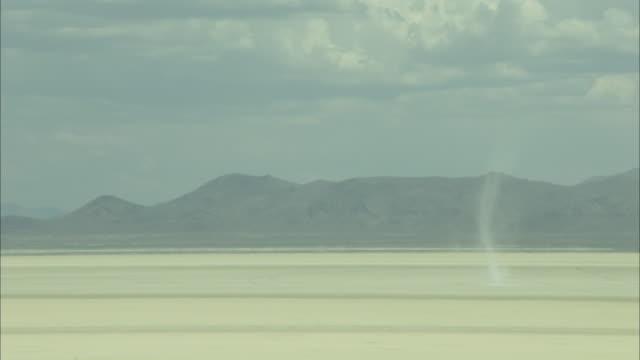 Thin dust devil spins across desert floor