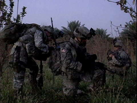 Third Infantry Division US soldiers kneeling in field and adjusting backpack at dawn / Arab Jabour Iraq / AUDIO