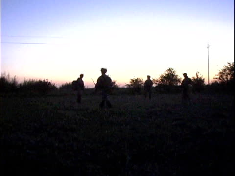 Third Infantry Division US soldiers patrolling field at dawn / Arab Jabour Iraq / AUDIO