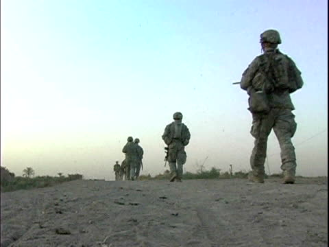 Third Infantry Division US soldiers walking on dirt road during patrol of remote area / Arab Jabour Iraq / AUDIO