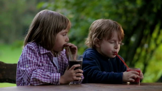 Thirsty Girl and boy drinking juice Outdoors