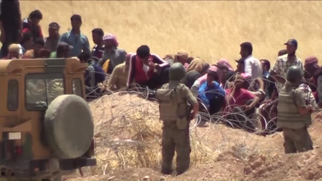 This footage recorded from Turkey's southeastern city Sanliurfa shows that a group of Syrians fled from clashes in Rasulayn region of Haseke wait at...
