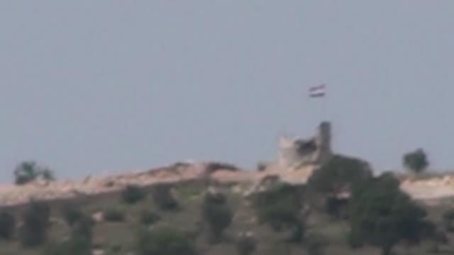 This footage taken from Turkey's Kilis province on May 13 2017 shows a Russian flag flying alongside with PYD symboşs on the top of a building that...