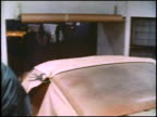 This is the first of 2 montages showing the assembly of American Motors' compact car the Hornet This montage shows factory workers spray painting...