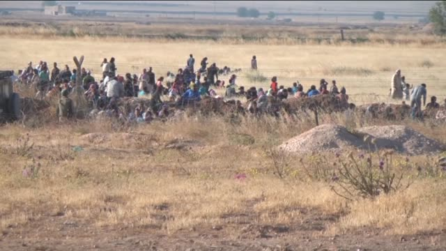 This video footaged from Suruc district of Turkey's Sanliurfa province shows a group of Syrians wait at Syrian side of Turkish border during the...
