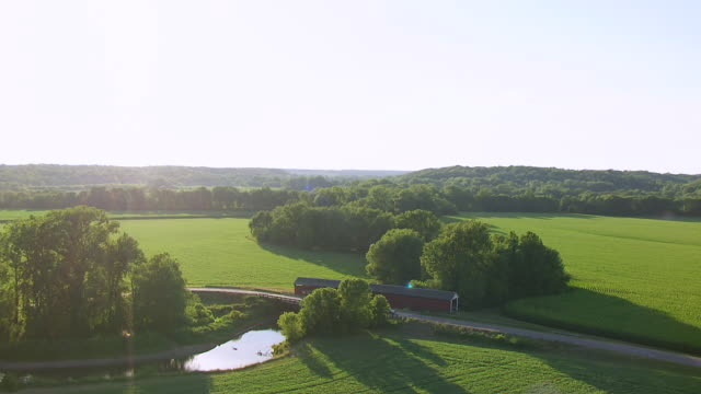 WS AERIAL POV Thorpe Ford Covered Bridge over river, farmland and forest area in background / Parke County, Rosedale, Indiana, United States