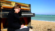 thoughtful young woman writing at the piano