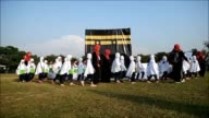 Thousands of Malaysian children take part in a practice run for the Muslim hajj pilgrimage walking round a model of the holy Kaaba shrine under the...