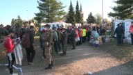 Thousands of migrants on Saturday gathered at a refugee camp in Dobova near the border between Croatia and Slovenia as they take respite during their...