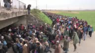 Thousands of migrants walk from the temporary camp of Rigonce to another provisional location in the village of Dobova as Slovenia faces the biggest...