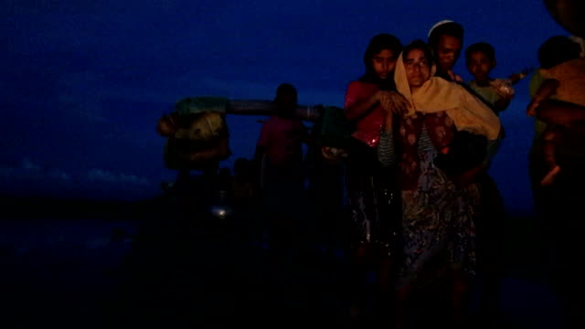 Thousands of Rohingya refugees fleeing from Myanmar walk along a muddy rice field after crossing the border in Palang Khali Cox's Bazar Bangladesh...
