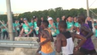 Thousands of runners in race head out over a bridge at start of 10K Elite runners head to finish line while fun runners head out in the other...