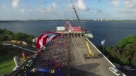 Thousands of runners in race head out over a bridge at start of 10K Aerial shot from drone with flag and runners