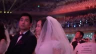 Thousands of Unification Church couples take part in a mass wedding to mark the fifth anniversary of the death of its founder Sun Myung Moon revered...