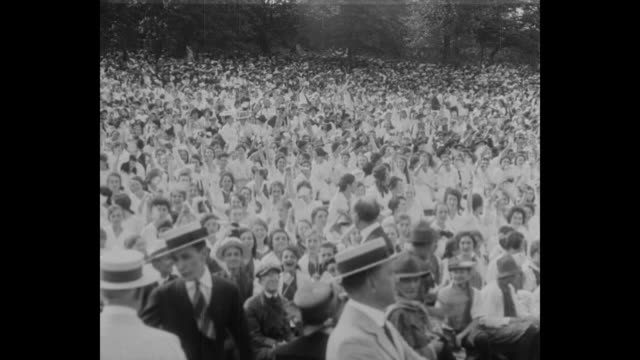 Thousands of white clad people wave flags / John Philip Sousa conducts his band / pan right of a crowd of young people waving flags and a different...