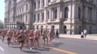 Thousands of women start running race in Albany NY a festive sports scene a pan down from NY State Capital Building