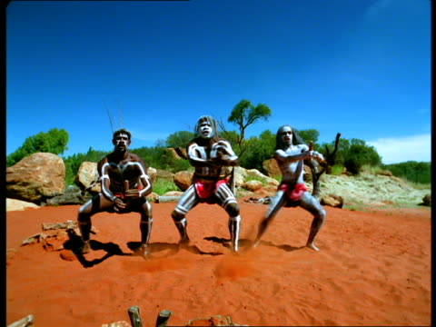 Three Aborigine men clap wooden sticks and kick up red dirt as they dance around.