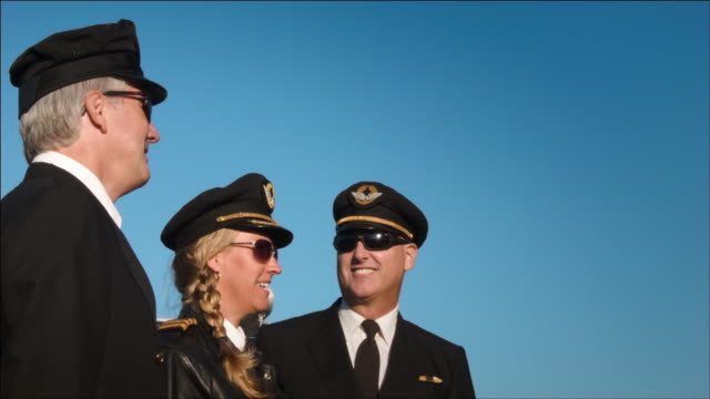 W/S three airline pilots, one female - two male, watch as airplane passes overhead: Boeing-747