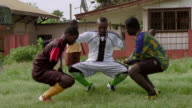 Three amputee soccer players squat as part of their workout. Available in HD.