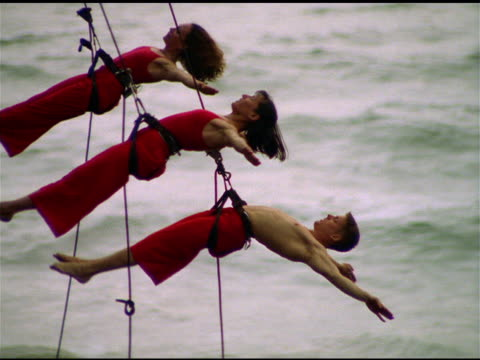 Three Bandaloop Project dancers wearing red and attached to safety harnesses leap off and onto cliff face as part of acrobatic routine, California