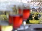 Three blurred wine glasses man fishing from rocks in distance Casablanca