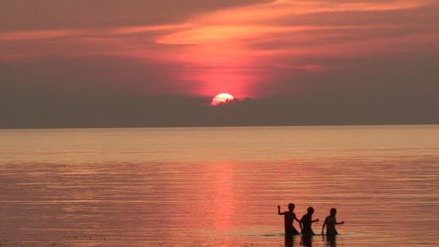 Three boys at sunset