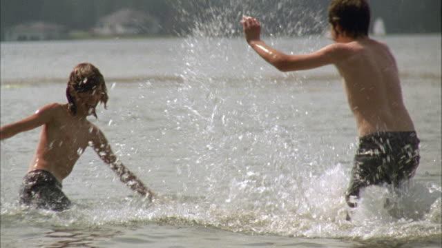 SLO MO MS PAN Three boys playfully splashing in lake / Cazenovia, New York, USA