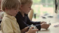 CU SELECTIVE FOCUS Three boys (4-5, 6-7, 8-9) playing video games / Portland, Maine, USA