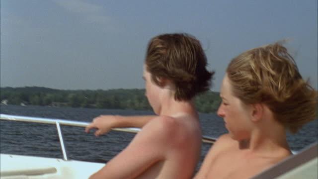 CU PAN Three boys riding on motorboat speeding across lake / Cazenovia, New York, USA