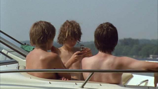 MS Three boys sitting on motorboat, one texting on his cell phone / Cazenovia, New York, USA