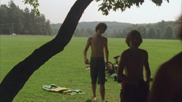 WS Three boys walking in park and removing their shirts / Cazenovia, New York, USA