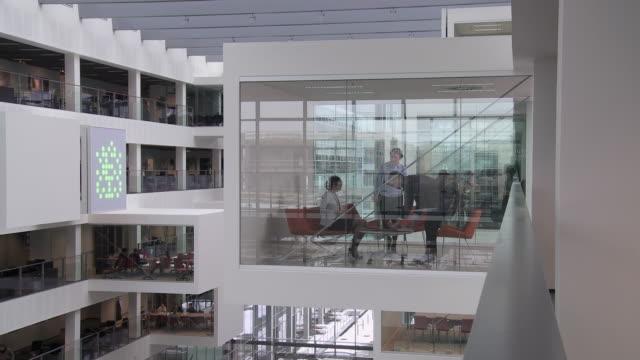 MS Three business people sitting at meeting in modern office, Copenhagen, Denmark
