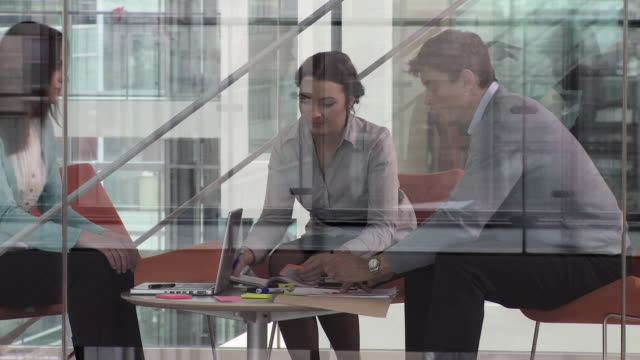 MS PAN Three business people sitting at meeting in modern office, Copenhagen, Denmark