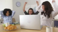 Three business women celebrating at good news while using laptop computer