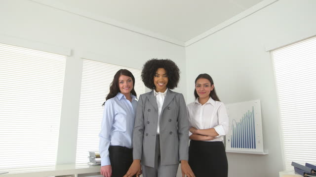 Three business women standing in office and smiling